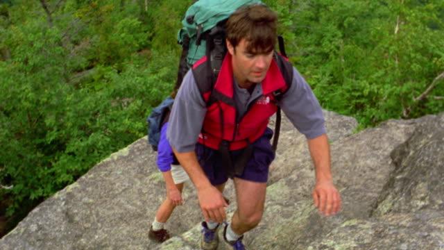 high angle couple with backpacks hiking up rocks / man helps woman up last few steps