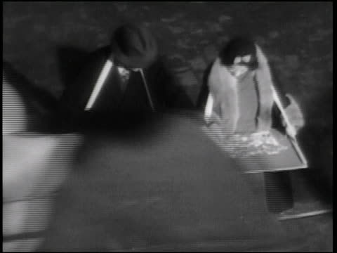 b/w 1938 high angle couple with trays around necks playing with jigsaw puzzles + walking on street / newsreel - jigsaw puzzle stock videos & royalty-free footage