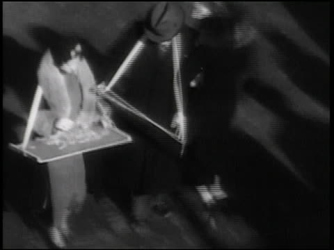 b/w 1938 high angle couple with trays around necks playing with jigsaw puzzles + crossing street / man spills - jigsaw puzzle stock videos & royalty-free footage