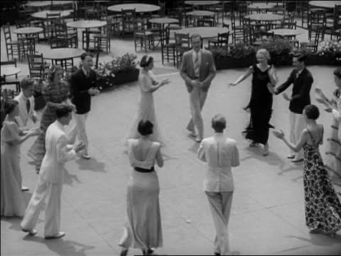 """B/W 1937 high angle couples in summer outfits dancing """"Big Apple"""" in circle outdoors / Washington, DC / newsreel"""
