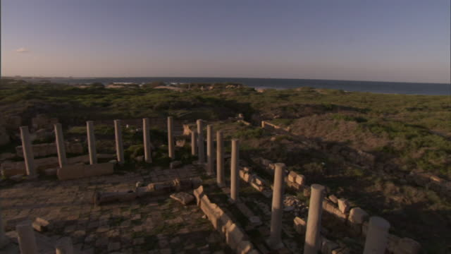High Angle crane pan-left push-in tracking-left - Shadows fall across the columns and other ruins of Leptis Magna. / Khoms, Libya