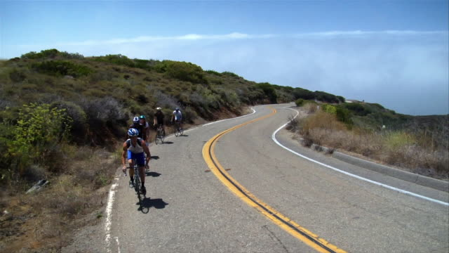 high angle crane shot group of cyclist biking uphill on winding road - five people stock videos & royalty-free footage