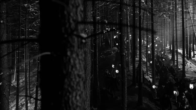 vídeos de stock, filmes e b-roll de high angle crane shot long shot mob carrying torches through forest at night - multidão violenta