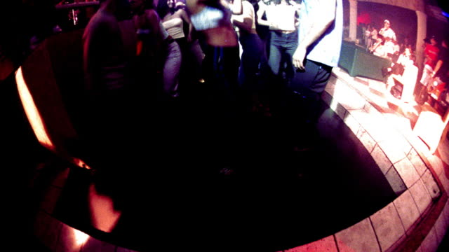 overexposed high angle crane shot time lapse people dancing on dance floor of nightclub with flashing lights - overexposed video stock e b–roll