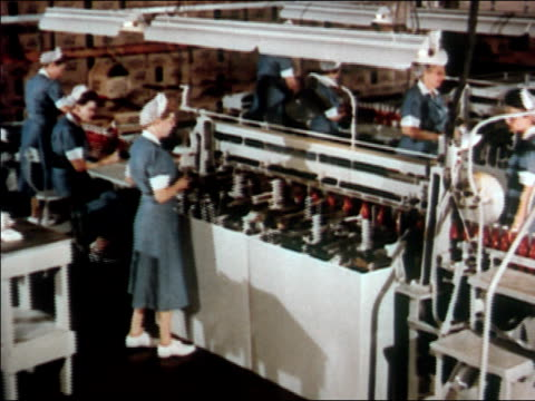 1951 high angle crane shot women working at ketchup bottling plant / zoom in close up machine placing labels on heinz ketchup bottles / audio - ketchup stock videos and b-roll footage