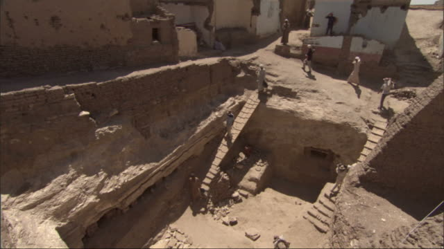 high angle, crane - workers descend a plank ladder into an archeological dig / egypt - archäologie stock-videos und b-roll-filmmaterial