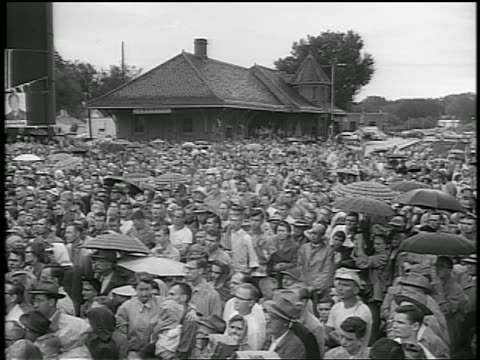 b/w 1952 high angle crowd at train station / some with umbrellas / eisenhower whistlestop campaign / newsreel - anno 1952 video stock e b–roll