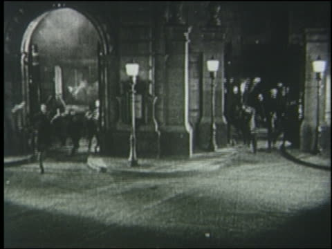 B/W 1925 high angle crowd carrying torches runs thru arches into street at night