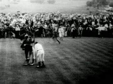 stockvideo's en b-roll-footage met high angle crowd congratulating winner johnny farrell on 18th green / mateson, il / u.s. open - 1928