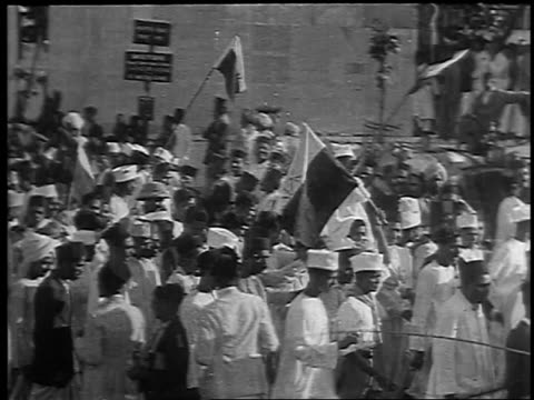 b/w 1930 high angle crowd marching with flags banners at antibritish rule demonstration / bombay india - 1930 bildbanksvideor och videomaterial från bakom kulisserna