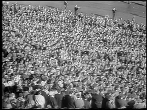 vídeos de stock e filmes b-roll de b/w 1965 high angle crowd of army cadets cheering in army vs navy football game / philadelphia / newsreel - cadete