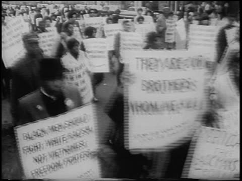 b/w 1967 high angle crowd of black antiwar demonstrators marching with signs / nyc / newsreel - peace demonstration stock videos and b-roll footage
