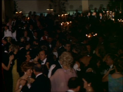 1965 high angle pan of crowd of couples in formalwear dancing / academy awards - 舞踏会点の映像素材/bロール