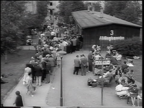 b/w 1961 high angle crowd of east german refugees in line at building / beginning of berlin wall - flüchten stock-videos und b-roll-filmmaterial