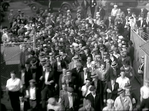 b/w 1937 high angle crowd of male workers entering factory thru factory gates - 1937 stock videos & royalty-free footage