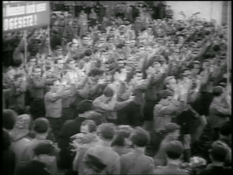 b/w 1950 high angle pan crowd of men clapping marching in communist demonstration / berlin / newsreel - konformität stock-videos und b-roll-filmmaterial