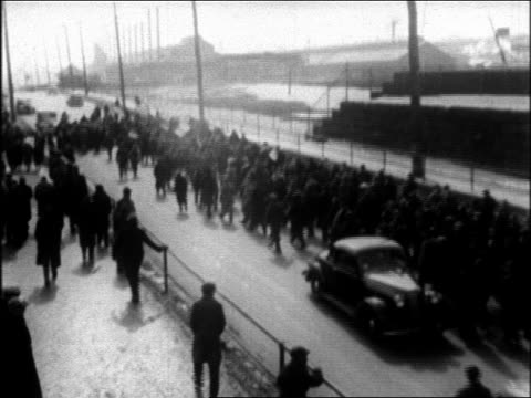 B/W 1937 high angle crowd of men walking on street next to fenced in factory during strike