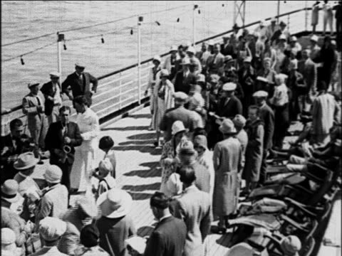 vídeos de stock, filmes e b-roll de b/w 1929 high angle crowd of passengers watching band on deck of s.s. honolulu cruise ship / newsreel - 1920 1929