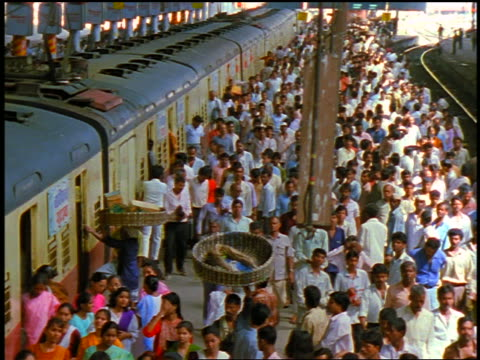 vidéos et rushes de high angle crowd of people entering + exiting train at train station / bombay, india - train de banlieue