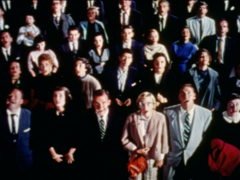 vidéos et rushes de 1956 high angle crowd of people sitting in chairs looking up with mouths open / industrial - surprise