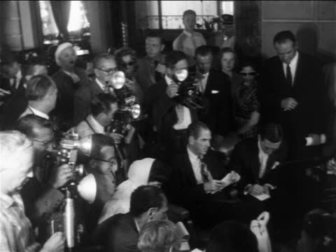 high angle crowd of reporters + photographers at news conference with elizabeth taylor + mike todd - 1957 stock-videos und b-roll-filmmaterial