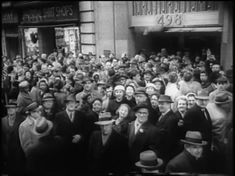 b/w 1958 high angle crowd of striking garment workers on city street looking at camera / newsreel - 労働組合点の映像素材/bロール