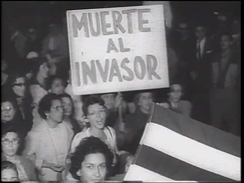 b/w 1962 high angle crowd of women carry muerte al invasor poster in demonstration / cuban missile crisis - cuban missile crisis stock videos & royalty-free footage