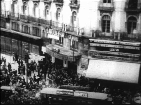 B/W 1931 high angle PAN crowd running past stopped trolleys in street during riot / Spain