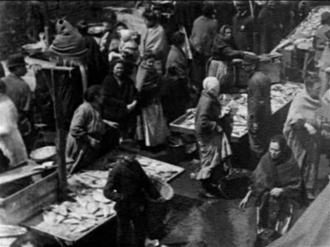 vídeos de stock e filmes b-roll de b/w 1903 high angle pan crowd shopping at pushcarts at ghetto fish market / lower east side, nyc / newsreel - 1903