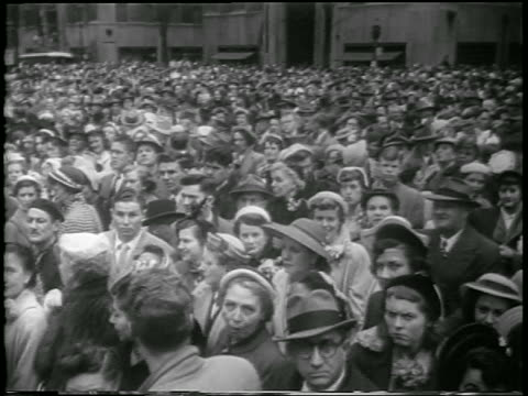 vídeos y material grabado en eventos de stock de b/w 1952 high angle pan crowd standing on new york city street / easter / newsreel - 1952