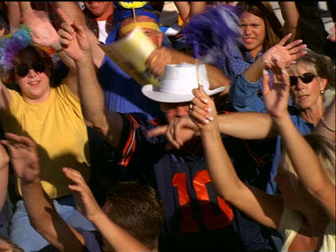 canted high angle pan crowd waving + cheering in stadium / men selling popcorn + beverages - bancarella video stock e b–roll