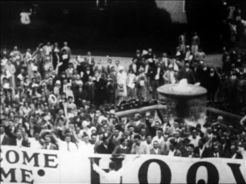 b/w 1928 high angle pan crowd with welcome home hoover sign by fountain / palo alto ca / newsreel - 1928 stock-videos und b-roll-filmmaterial