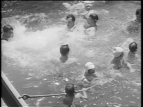 b/w 1934 high angle cruise ship passengers splashing + playing in swimming pool - 1934 stock videos & royalty-free footage