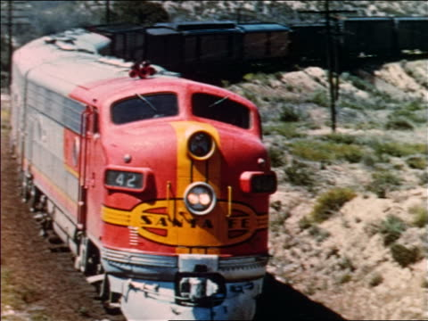 vídeos y material grabado en eventos de stock de 1954 high angle pan diesel freight train rounding curve in desert-like area / industrial - 1954