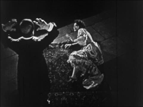 vídeos de stock e filmes b-roll de b/w 1925 high angle disfigured man (lon chaney, sr.) reaching for woman (mary philbin) on floor / feature - 1925