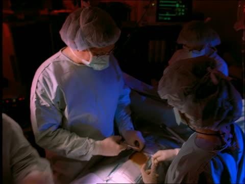 vídeos de stock e filmes b-roll de high angle pan of doctors + nurses in surgery - bata cirúrgica