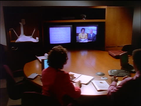 high angle dolly shot behind businesswomen + businessman having teleconference