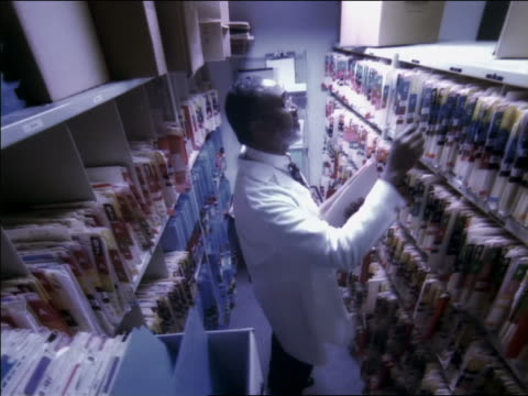 high angle dolly shot black male doctor in lab coat between rows of file cabinets closing one file and pulling another - nur männer über 40 stock-videos und b-roll-filmmaterial