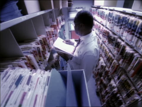 High angle dolly shot Black male doctor in lab coat standing between two rows of file cabinets looking at file