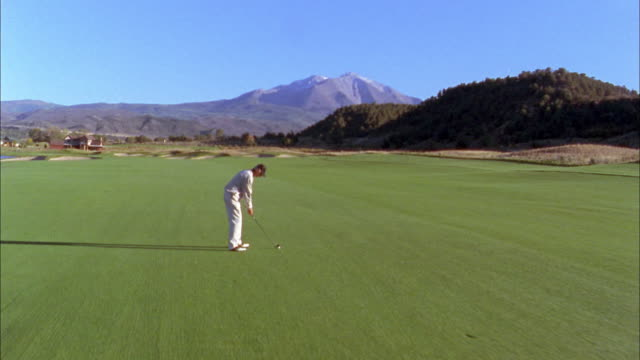 high angle dolly shot male golfer hitting drive on golf course w/mountain in background - teeing off stock videos & royalty-free footage