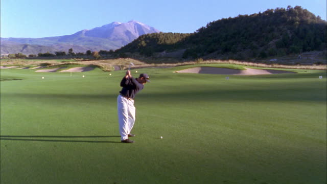 high angle dolly shot male golfer hitting drive on golf course w/mountain in background - golf shot stock videos & royalty-free footage