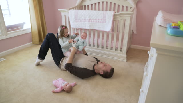 stockvideo's en b-roll-footage met high angle dolly shot of father and daughter playing with doll on floor at home - genderblend