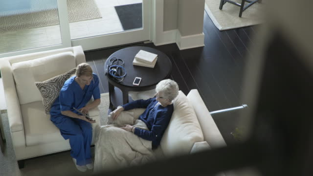 High angle dolly shot of senior woman and home caregiver using tablet computer in living room