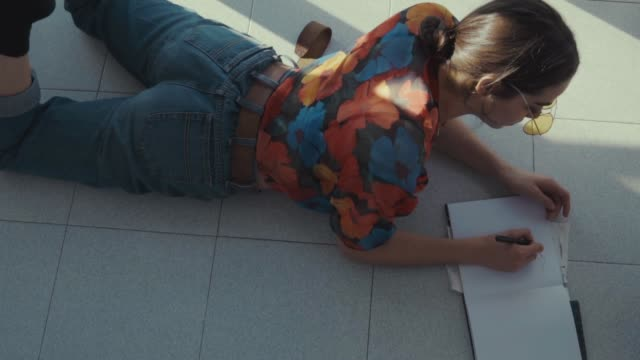 stockvideo's en b-roll-footage met high angle dolly shot of woman drawing while lying on floor at home - op de buik liggen