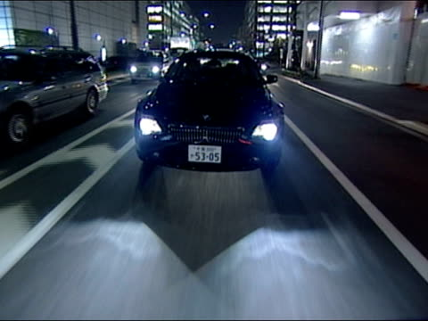 High angle dolly shot rear point of view car driving along city streets at night / Tokyo, Japan