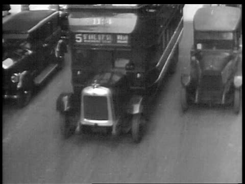 B/W 1927 high angle double decker bus on city street / educational