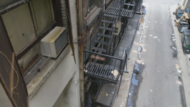 high angle down of fire escape landing and alley. garbage dumpsters visbile.