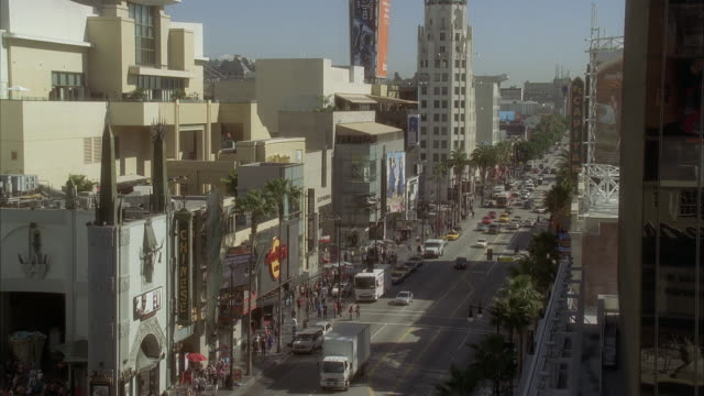 high angle down of hollywood boulevard and grauman's chinese theater. movie theater, multi-story and high rise office or apartment buildings. crowds of people, pedestrians, tourists. landmarks. cars on city street. los angeles area. - hollywood boulevard stock videos and b-roll footage