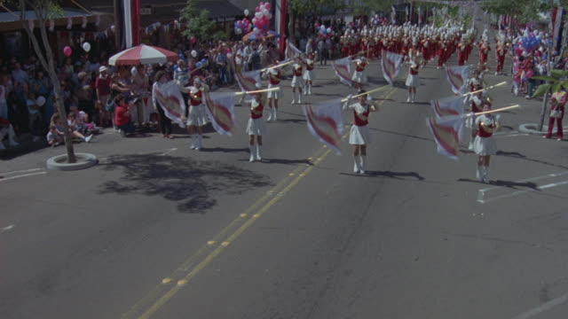 High angle down of parade with marching band and colorguard with sign that reads fountain valley high school. parade moves to left, float at end reads our queen and court.