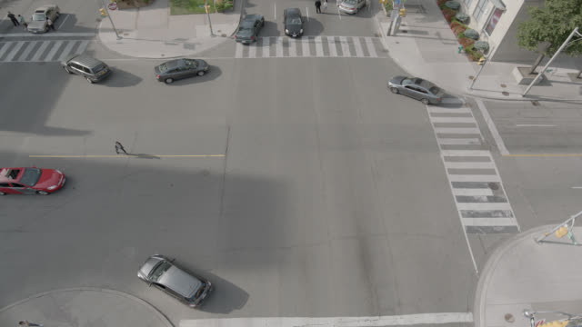 high angle down of people running or fleeing in city street. intersection and cars visible. - escaping stock videos & royalty-free footage